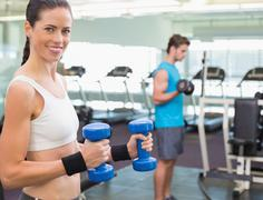 Fit brunette exercising with blue dumbbells - stock photo
