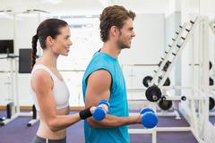 Fit couple exercising with blue dumbbells - stock photo
