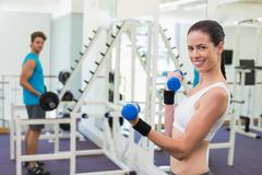 Stock Photo of Fit brunette exercising with blue dumbbells