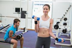 Fit brunette exercising with blue dumbbells smiling at camera - stock photo