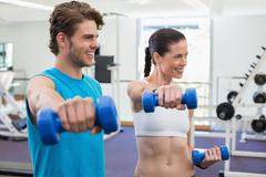 Fit couple exercising with blue dumbbells and smiling - stock photo
