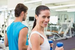 Fit couple exercising together with blue dumbbells - stock photo