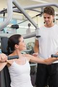 Stock Photo of Fit brunette using weights machine for arms with trainer helping