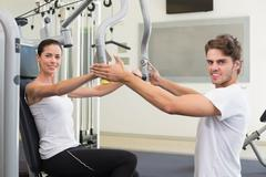 Stock Photo of Fit brunette using weights machine for arms with trainer helping smiling at