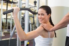 Stock Photo of Fit brunette using weights machine for arms with trainer touching shoulders