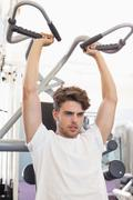 Stock Photo of Fit focused man using weights machine for arms