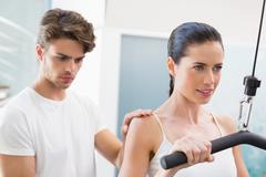 Fit smiling woman using weights machine for arms with her trainer - stock photo