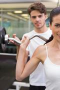 Stock Photo of Fit smiling woman lifting barbell with her trainer
