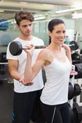 Fit smiling woman lifting barbell with her trainer - stock photo