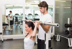 Stock Photo of Fit woman lifting barbell with her trainer spotting