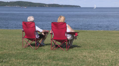 Older retired baby boomers sitting in lawn chair by the lake - stock footage