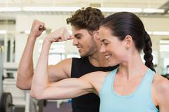 Stock Photo of Fit attractive couple comparing biceps