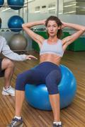 Trainer helping his client doing sit up on exercise ball - stock photo