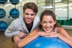 Stock Photo of Fit woman leaning on exercise ball with trainer smiling at camera