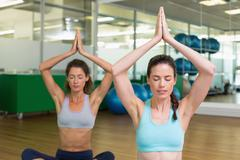 Fit women doing yoga together in studio Stock Photos