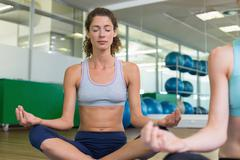 Fit women doing yoga together in studio - stock photo