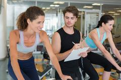 Stock Photo of Fit women in a spin class with trainer taking notes
