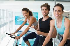 Fit women in a spin class with trainer taking notes and smiling at camera Stock Photos