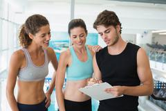 Stock Photo of Fit women with trainer taking notes and smiling at camera