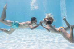 Cute couple kissing underwater in the swimming pool - stock photo