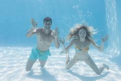 Cute couple smiling at camera underwater in the swimming pool - stock photo