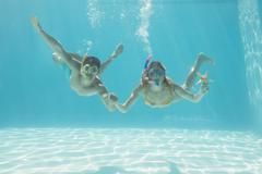 Cute couple underwater in the swimming pool with snorkel and starfish - stock photo