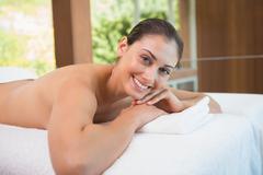 Beautiful brunette lying on massage table smiling at camera - stock photo