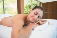Beautiful brunette lying on massage table with eyes closed Stock Photos