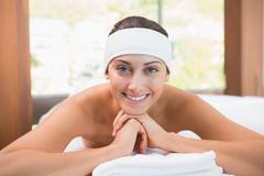 Stock Photo of Beautiful smiling brunette lying on massage table