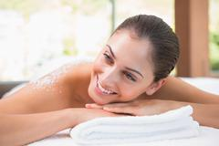 Beautiful smiling brunette lying on massage table with salt scrub on back Stock Photos