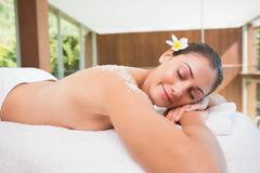 Beautiful brunette lying on massage table with salt scrub on back Stock Photos