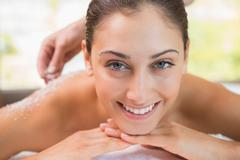 Beauty therapist pouring salt scrub on smiling womans back - stock photo