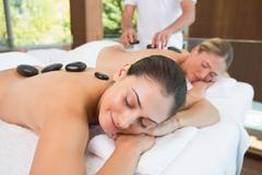 Stock Photo of Calm friends lying on massage tables with hot stones on their backs