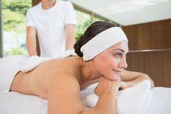 Beauty therapist rubbing smiling womans back with heated mitts - stock photo
