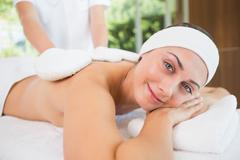 Stock Photo of Beauty therapist rubbing smiling womans back with heated mitts