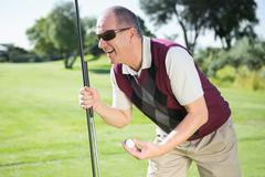 Stock Photo of Excited golfer holding ball and club