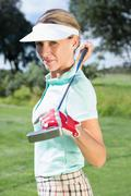 Stock Photo of Female golfer standing holding her club smiling at camera