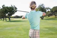 Stock Photo of Female golfer taking a shot