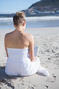 Content blonde in white dress sitting on the beach reading book Stock Photos
