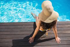 Beautiful brunette in bikini sitting by the pool paddling - stock photo