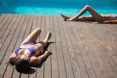 Women in bikinis lying poolside sunbathing Stock Photos