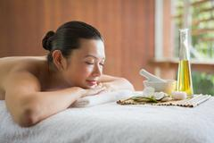 Stock Photo of Brunette lying on massage table with tray of beauty treatments