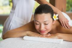 Brunette enjoying a peaceful massage with eyes closed Stock Photos