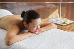 Stock Photo of Content brunette relaxing on massage table