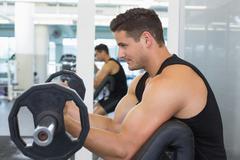 Stock Photo of Focused bodybuilder lifting heavy black barbell