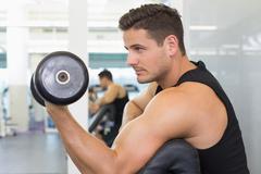 Stock Photo of Focused bodybuilder lifting heavy black dumbbell