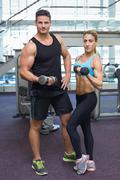 Bodybuilding man and woman holding dumbbells looking at camera Stock Photos