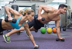 Bodybuilding man and woman holding dumbbells in plank position Stock Photos