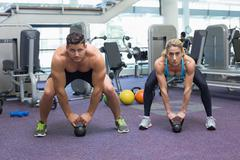 Bodybuilding man and woman lifting kettlebells in a squat Stock Photos