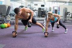Bodybuilding man and woman lifting kettlebells in plank position Stock Photos